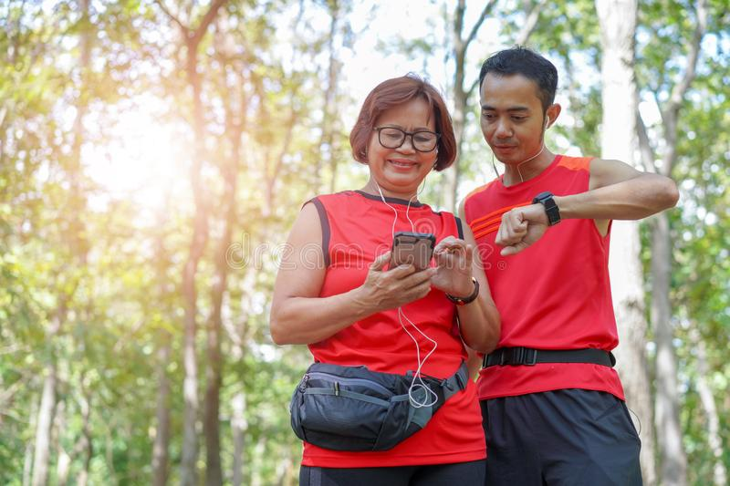 Happy senior asian woman with man or personal trainer checking time from smart watch stock photo