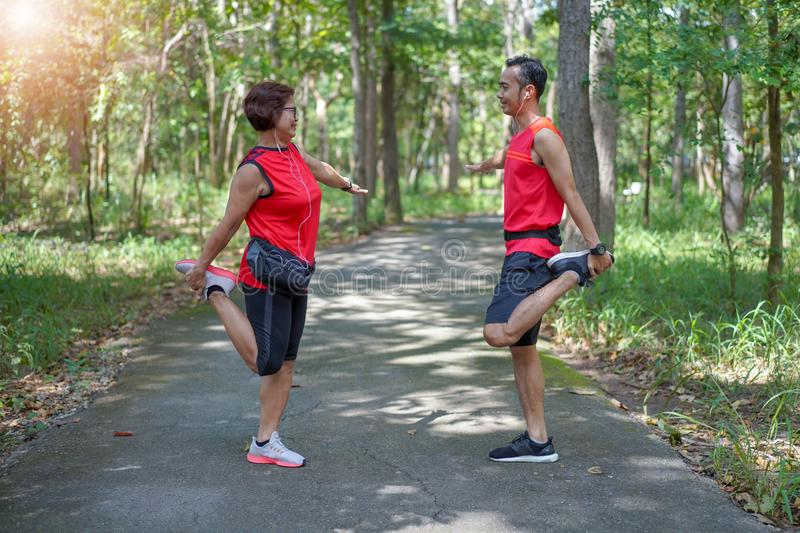 Happy senior asian woman with man or personal trainer stretch thigh muscles at park stock photos