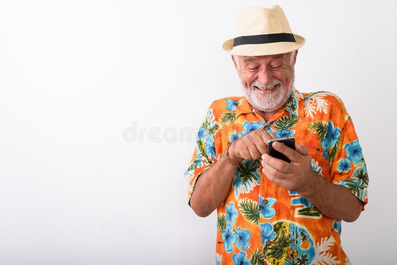 Happy senior bearded tourist man smiling and giggling while using phone stock image