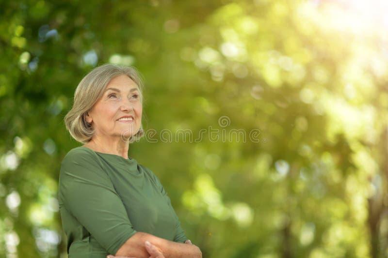 Happy senior beautiful woman in spring park royalty free stock image