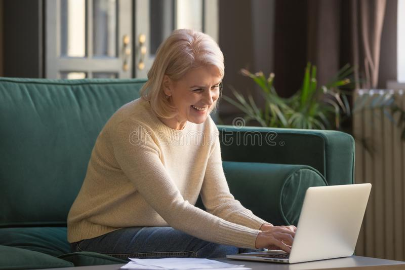 Smiling senior woman feel free using laptop at home royalty free stock images