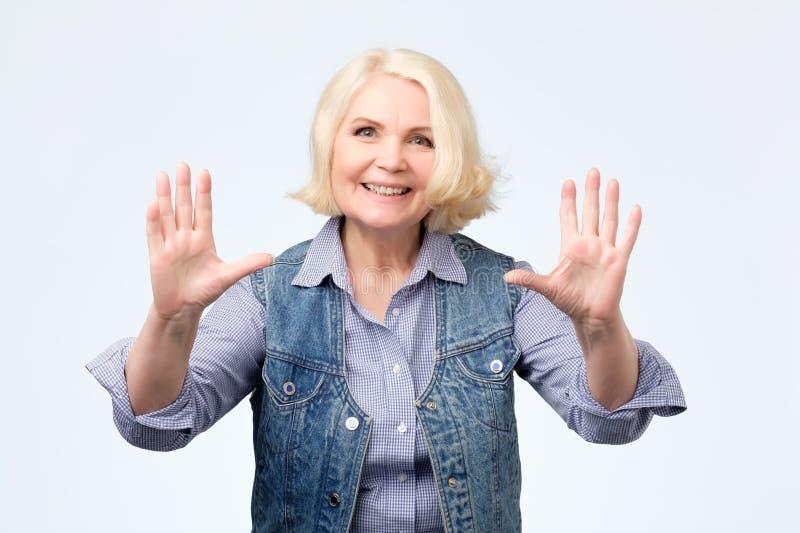 Happy senior blonde woman showing ten fingers. stock photos