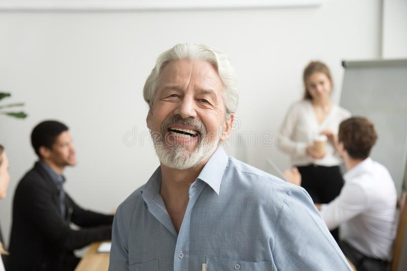 Happy senior businessman laughing looking at camera in office, p stock images