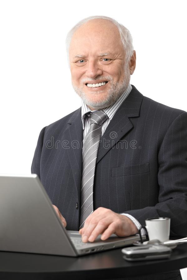 Happy senior businessman using computer royalty free stock image