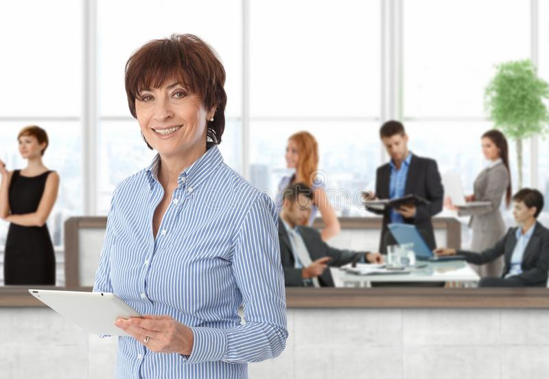 Happy senior businesswoman with working team. Happy senior businesswoman with team of working businesspeople at office royalty free stock photos
