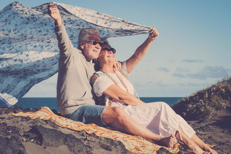Happy senior caucasian couple enjoy the outdoor leisure activity together - active old people in love have fun under the sun - royalty free stock photos