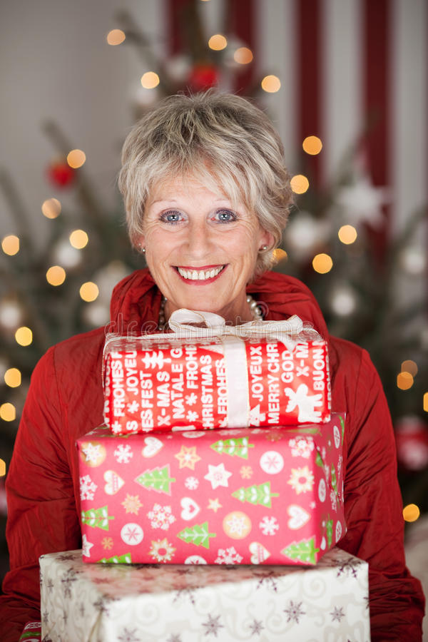Happy senior with Christmas gifts. Happy smiling beautiful senior lady with a stack of Christmas gifts sitting in front of a decorated Christmas tree with a royalty free stock photo