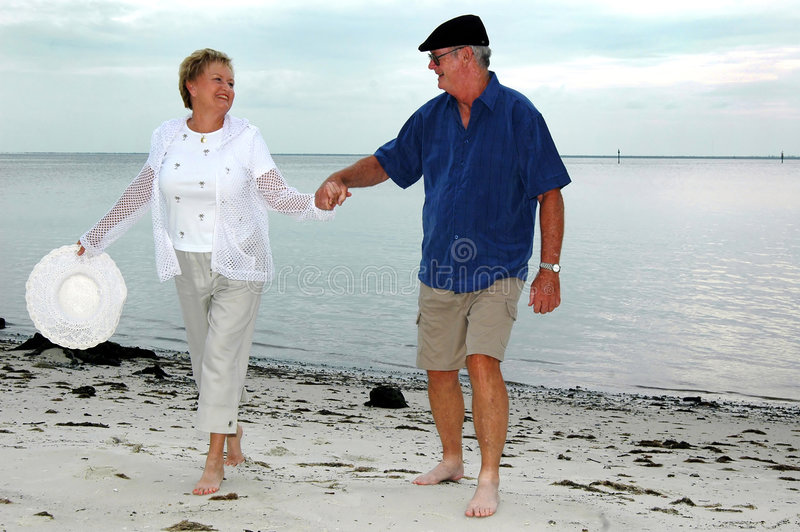 Happy senior couple on beach. A mature couple walking hand in hand at the beach