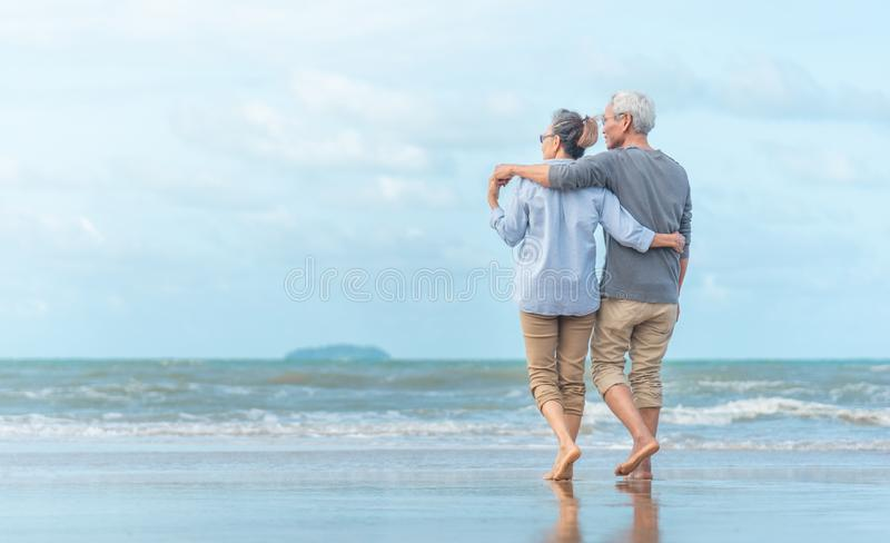 Happy senior couple on the beach. Exotic luxury resort.back view stock photography