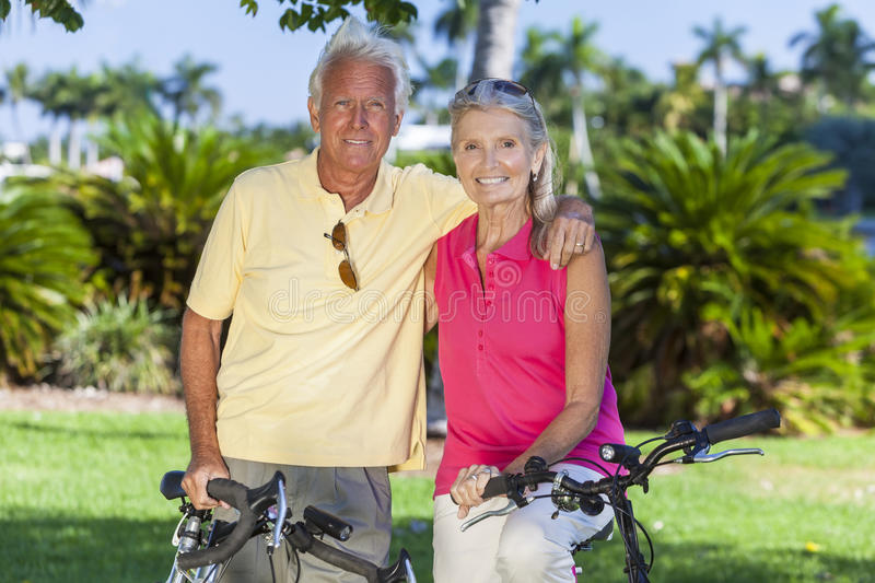 Happy Senior Couple on Bicycles In Park. Happy senior men and women couple together cycling on bicycles in a sunny green park royalty free stock photos
