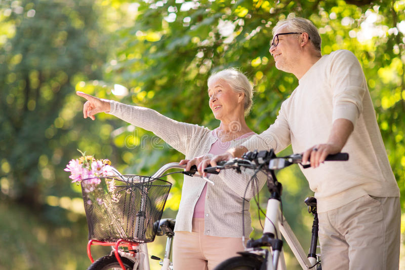 Happy senior couple with bicycles at summer park stock images