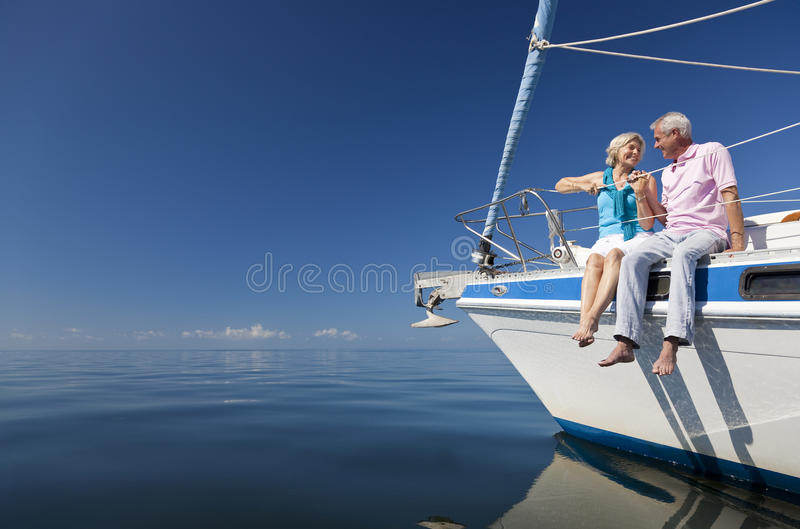 Happy Senior Couple on the Bow of a Sail Boat royalty free stock photos