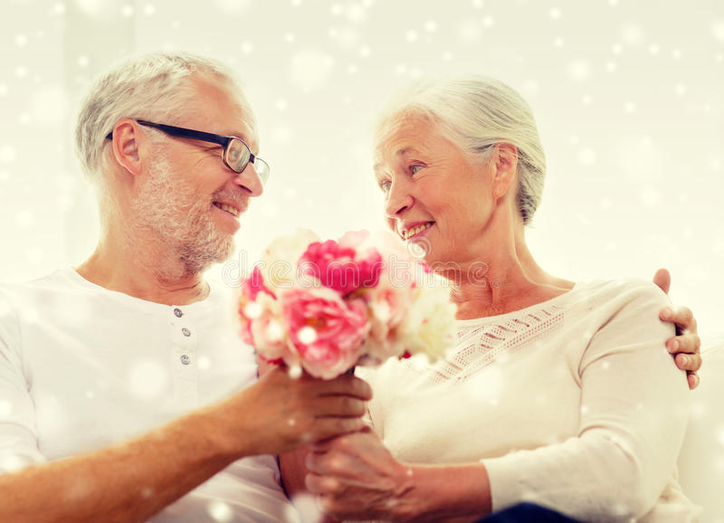 Happy senior couple with bunch of flowers at home. Family, holidays, age and people concept - happy senior couple with bunch of flowers at home royalty free stock photography