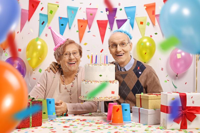 Happy senior couple with a cake at a birthday. Celebration stock images