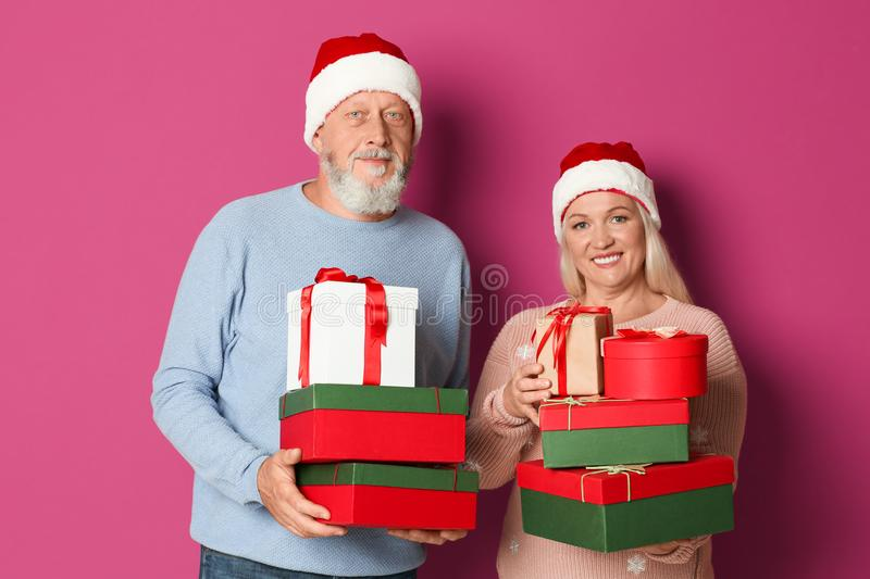 Happy senior couple with Christmas gifts on color background royalty free stock images