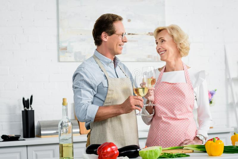 happy senior couple clinking with glasses of wine during cooking at kitchen and looking stock image