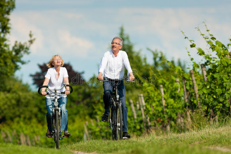 Happy senior couple cycling outdoors in summer stock images