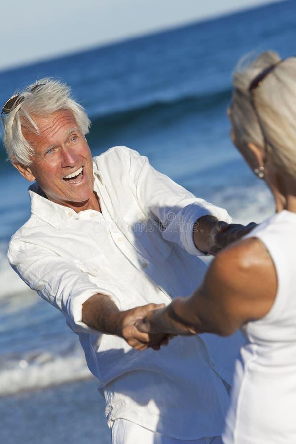 Happy Senior Couple Dancing Holding Hands Beach