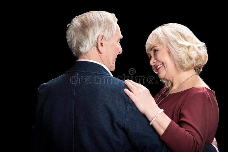 Happy senior couple dancing and looking at each other on black stock image