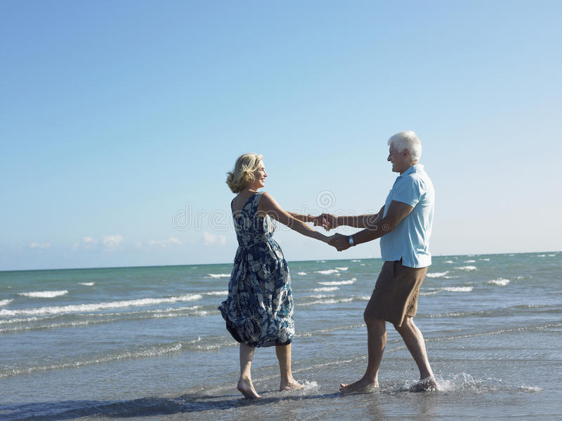 Happy Senior Couple Dancing On Tropical Beach stock photo