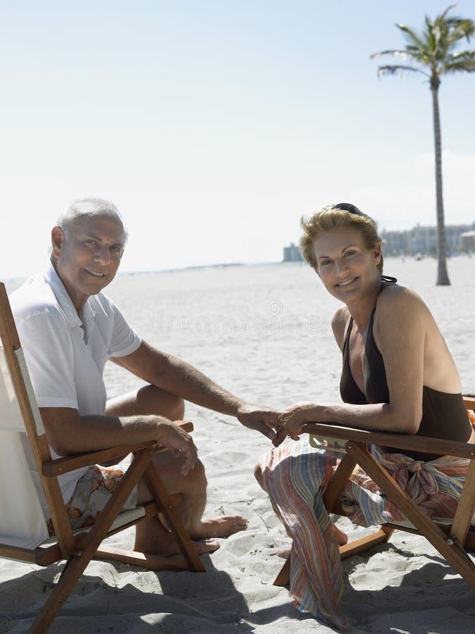 Happy Senior Couple On Deckchairs At Beach stock photos