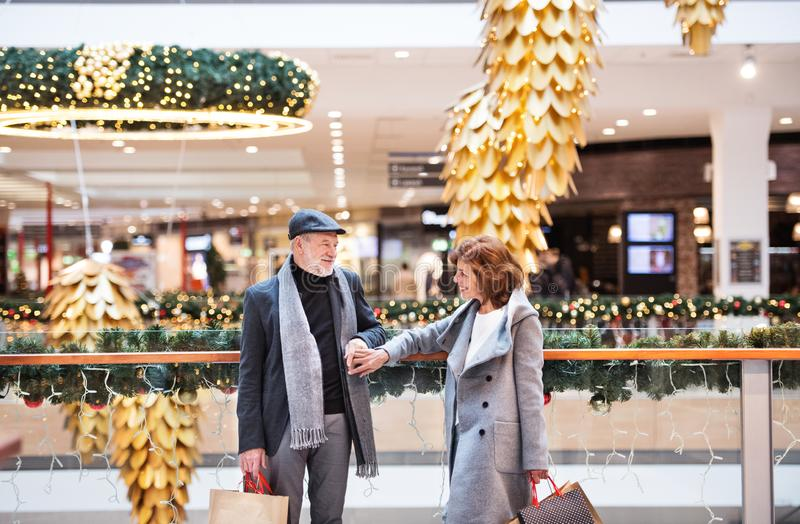 Happy senior couple doing Christmas shopping together. Senior couple doing Christmas shopping, holding hands. Shopping center at Christmas time royalty free stock image