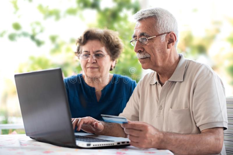 Happy Senior Couple Doing Online Shopping Using Credit Card Outdoors in Garden or in Cafe royalty free stock photo
