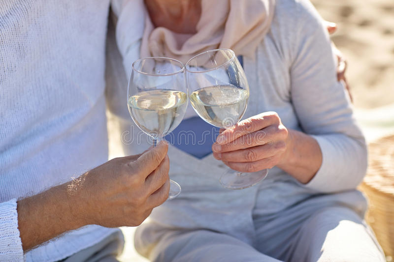 Happy senior couple drinking wine on summer beach royalty free stock image