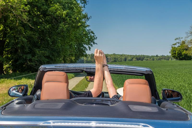 Happy senior couple driving modern car on their vacation trip. Two happy elderly people drives with a luxury convertible car on a sunny day stock photo