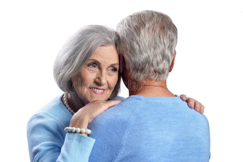 Happy senior couple embracing and posing on white background stock images