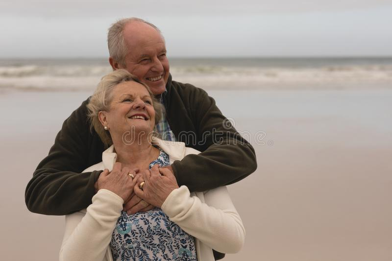 Happy senior couple embracing standing at the the beach royalty free stock image