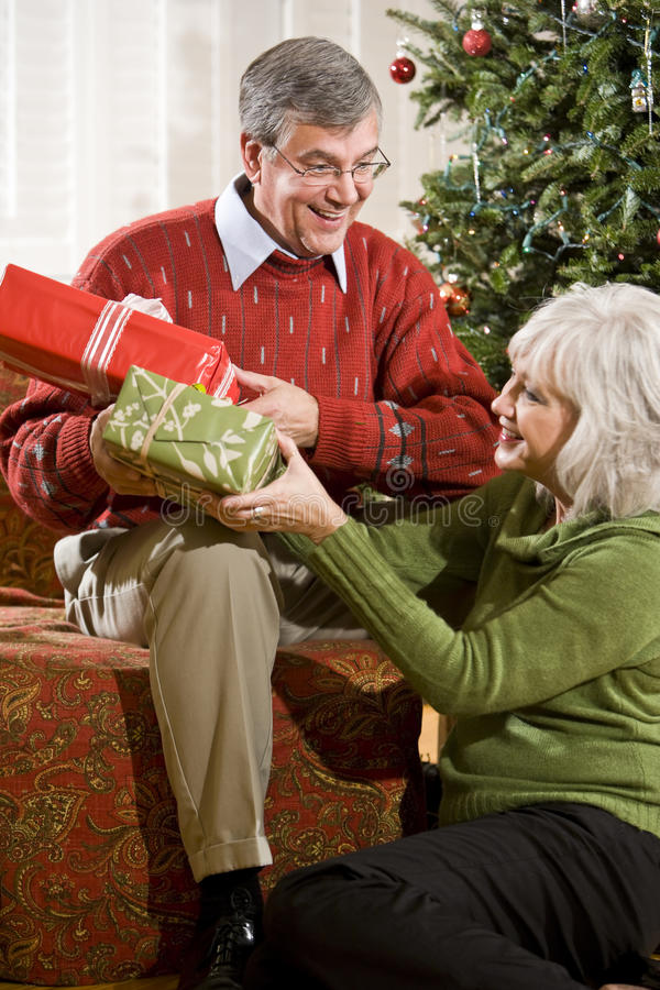 Happy senior couple exchanging Christmas gifts. At home by tree stock photos