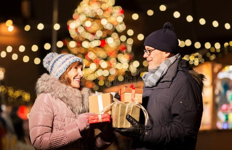 Happy senior couple with gift at christmas market. Love, winter holidays and people concept - happy senior couple with gift at christmas market on town hall stock images