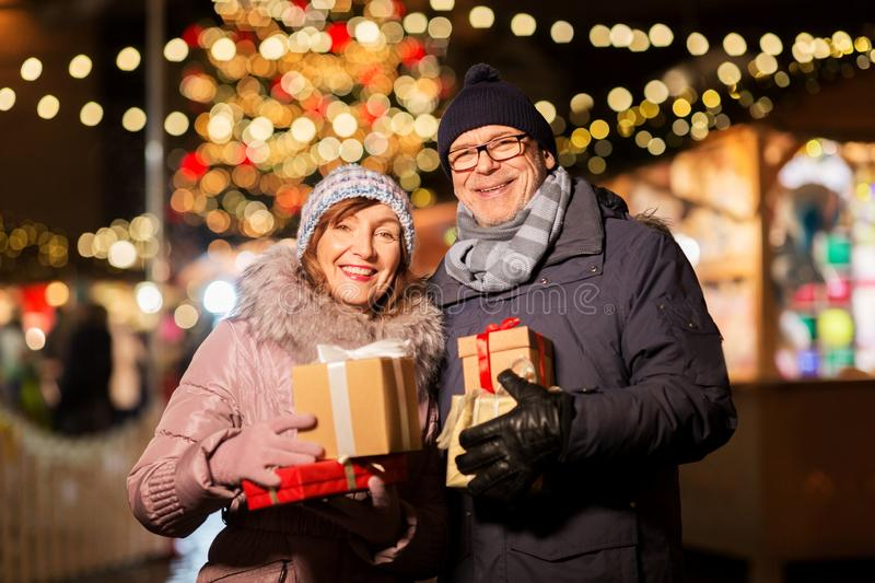 Happy senior couple with gift at christmas market. Love, winter holidays and people concept - happy senior couple with gift at christmas market on town hall royalty free stock photography