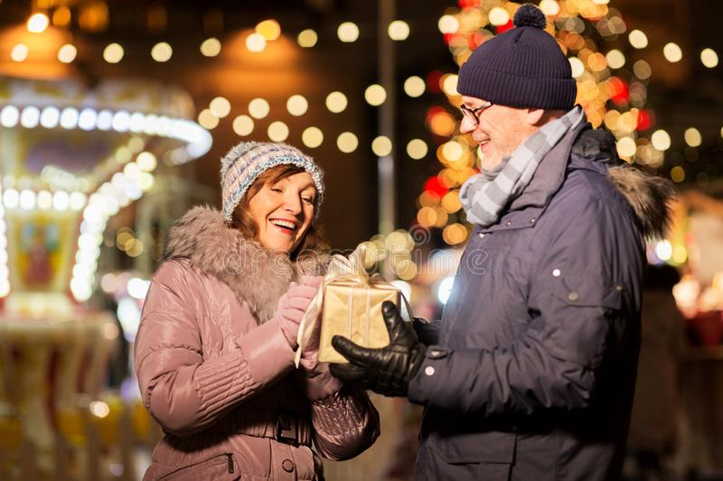 Happy senior couple with gift at christmas market. Love, winter holidays and people concept - happy senior couple with gift at christmas market on town hall royalty free stock photo
