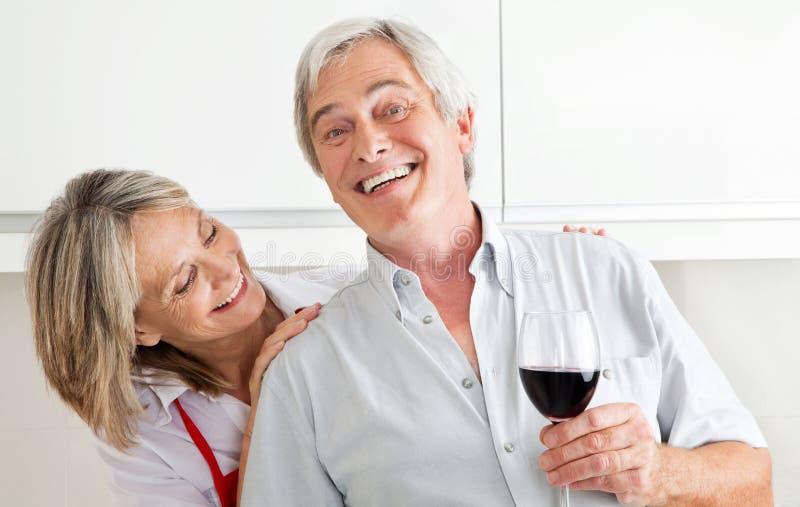 Happy senior couple with glass stock image