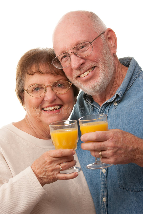 Happy Senior Couple with Glasses of Orange Juice. Isolated on a White Background royalty free stock images