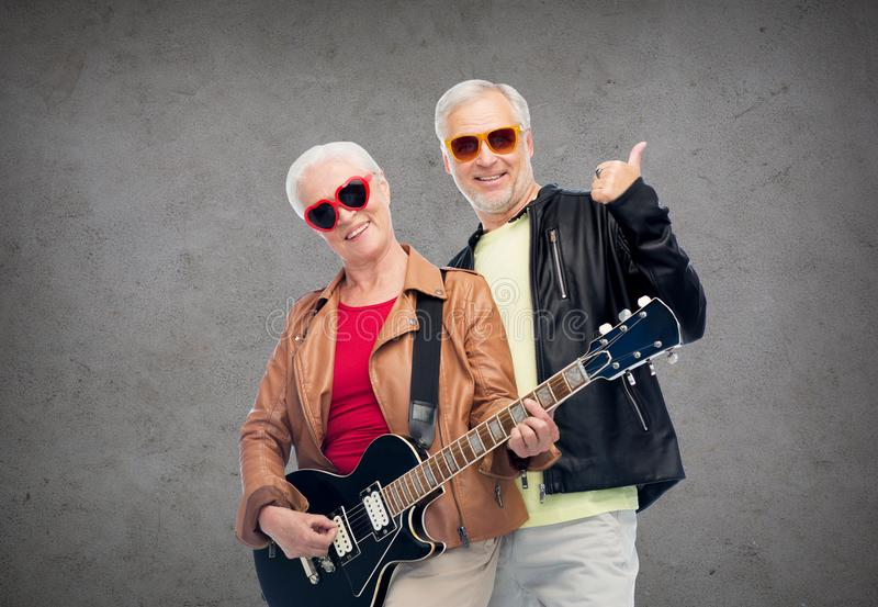 Happy senior couple with guitar showing thumbs up. Music, age and people concept - happy senior couple in sunglasses with electric guitar showing thumbs up over stock photos