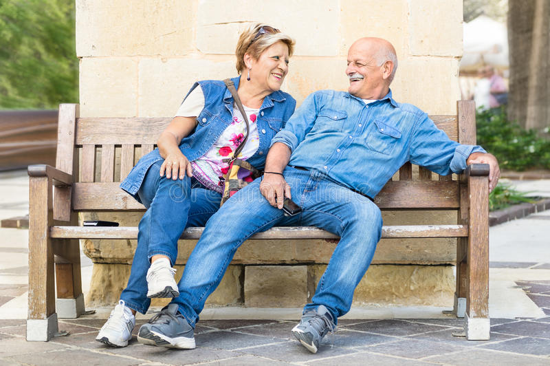 Happy senior couple having fun on a bench - Concept of active pl. Ayful elderly during retirement - Everyday lifestyle in autumn sunny afternoon royalty free stock images