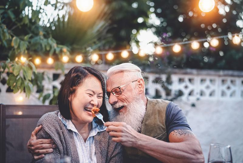 Happy senior couple having fun at dinner house party - Older people with different ethnicity doing a romantic date. For celebrating anniversary - Elderly, food stock photos