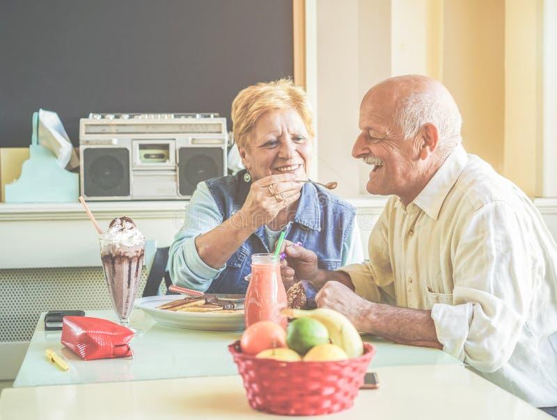 Happy senior couple having fun eating pancakes during united states vacation - Mature people enjoying brunch at bar restaurant -. Active elderly and travel stock photo