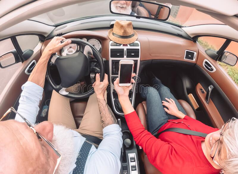 Happy senior couple having fun on new convertible car - Mature people enjoying time together during road trip vacation royalty free stock photography