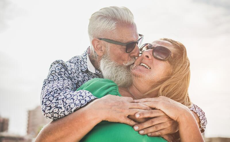 Happy senior couple having tender moments outdoor durin holiday trip - Old people lovers having fun together on anniversary. Vacation - Travel, relationship and stock photography