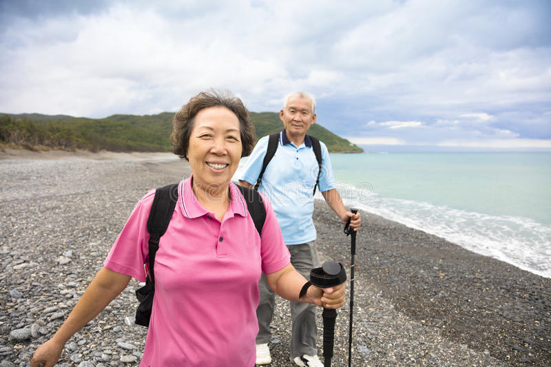 Happy senior couple hiking on the coast beach stock images