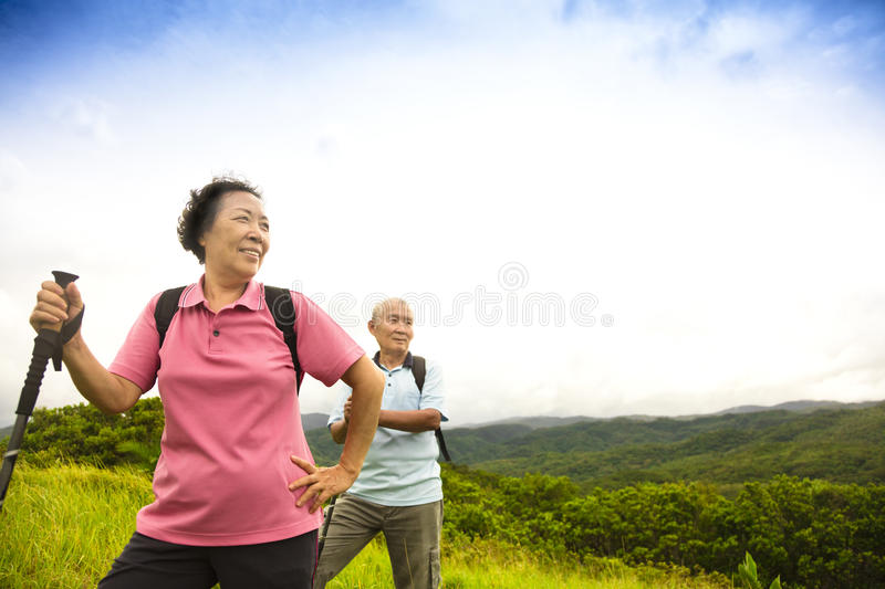 Happy senior couple hiking on the mountain royalty free stock photography