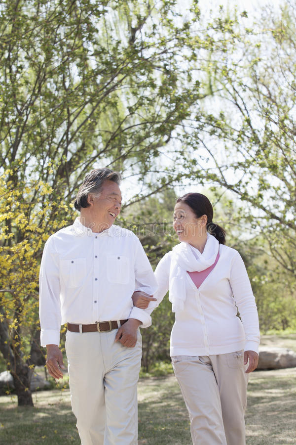 Happy senior couple holding hands and going for a walk in the park in springtime, Beijing royalty free stock photo