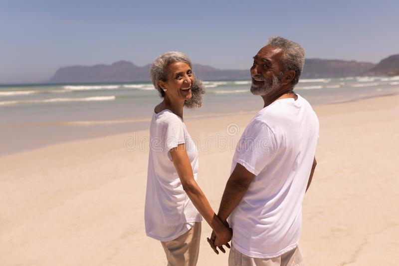 Happy senior couple holding hands and looking at camera on beach royalty free stock photography