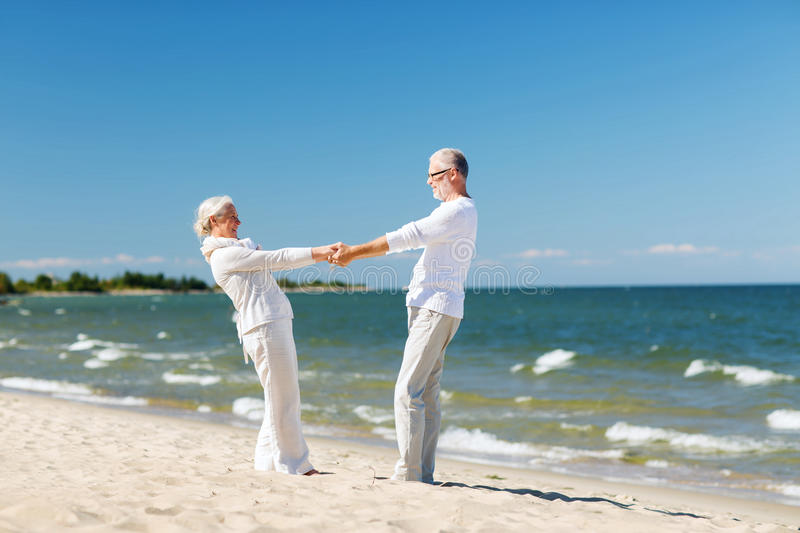 Happy senior couple holding hands on summer beach stock images