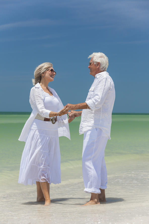Happy Senior Couple Holding Hands On Tropical Beach Stock Photography