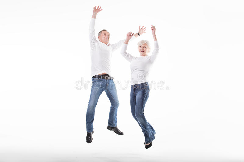 Happy senior couple jumping. stock photos